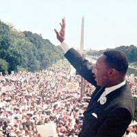 Photo - In this Aug. 28, 1963 archive photo, The Rev. Martin Luther King Jr. waves to the crowd at the Lincoln Memorial for his