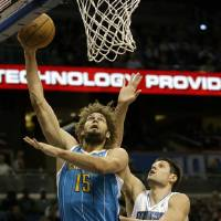 Photo - New Orleans Hornets' Robin Lopez (15) gets off a shot in front of Orlando Magic's Nikola Vucevic (9), of Montenegro, during the first half of an NBA basketball game on Wednesday, Dec. 26, 2012, in Orlando, Fla. (AP Photo/John Raoux)