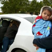 Photo - Claudia Perez holds 16-month-old son Matthew Perez Saturday while a Norman police officer checks to ensure a child safety seat is installed correctly. PHOTO BY CONNIE HEFNER, FOR THE OKLAHOMAN  Connie Hefner