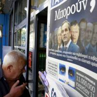 Photo -   A man enters a kiosk that sells newspapers as the newspaper on the right shows the new Greek government, in Athens, Friday, June 22, 2012. Greek authorities say the country's new prime minister, Antonis Samaras, will undergo eye surgery this weekend for a detached retina discovered during a routine examination.(AP Photo/Petros Karadjias)