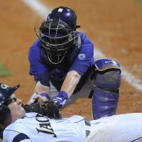 Photo - Georgia Tech's Daniel Spingola (35) is tagged out by Washington's Parker Guinn (26) trying to score on an infield ground ball to third base at the NCAA Oxford Regional at Oxford-University Stadium on Sunday, June 1, 2014. (AP Photo/Oxford Eagle, Bruce Newman)   NO SALES