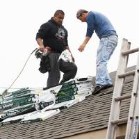 Photo - Workers install the roof of a house on SE 26 by Central Oklahoma Habitat for Humanity. Malarkey Roofing Products donated the roofing materials for 40 Habitat houses to be built this year.  NATE BILLINGS - The Oklahoman