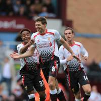 Photo - Liverpool's Steven Gerrard (centre) celebrates after scoring his team's opening goal during their English Premier League match against West Ham at Upton Park, London,  Sunday, April 6, 2014.   (AP Photo / Nick Potts,PA)  UNITED KINGDOM OUT  NO SALES  NO ARCHIVE