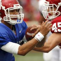 Photo - Quarterback Kendal Thompson keeps the ball and is challenged by Caleb Gastelum (45) during the OU football team's annual Red and White Game at Gaylord Family - Oklahoma Memorial Stadium on Saturday, April 14, 2012, in Norman, Okla.  Photo by Steve Sisney, The Oklahoman