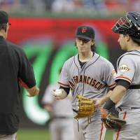 Photo - San Francisco Giants manager Bruce Bochy, left, removes pitcher Tim Lincecum, center, from a baseball game against the Washington Nationals during the third inning as Giants catcher Andrew Susac, right, stands by on Saturday, Aug. 23, 2014, in Washington. The Nationals won 6-2.  (AP Photo/Luis M. Alvarez)