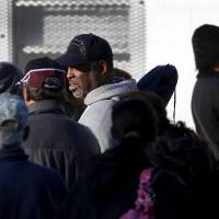 Photo - People wait in a long line to receive a turkey and a food basket. Jesus House distributed turkeys and grocery items Tuesday morning,  Nov. 19, 2012. Officials said they had 400 turkeys and food baskets to distribute and people were standing in line when their doors opened at 8 a.m. In less than two yours, all turkeys had been claimed. They will pass out 400 more turkeys and food baskets on Wednesday.  Photo by Jim Beckel, The Oklahoman