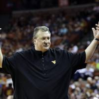 Photo - West Virginia coach Bob Huggins throws his arms up during the second half of an NCAA college basketball game against Texas, Saturday, Feb. 15, 2014, in Austin, Texas. Texas won 88-71. (AP Photo/Eric Gay)