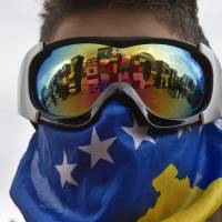 Photo - A Kosovo Albanian youth wearing ski goggles and a Kosovo flag stands near the
