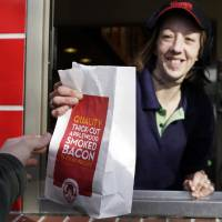 Photo -   FILE - In this Feb. 28, 2012 file photo a bag of fries is handed to a customer through the drive through window at a Wendy's restaurant in Falmouth, Maine. Wendy's push to remake itself as a higher-end hamburger chain is starting to pay off, with a key sales figure rising for the sixth straight quarter. The company, based in Dublin, Ohio, is trying to pull away from the image of the typical fast-food chain and cast itself as a purveyor of higher-quality burgers and sides. The move reflects the growing popularity of chains such as Chipotle and Panera, which offer better quality food for slightly higher prices. (AP Photo/Pat Wellenbach, File)