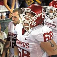 Photo - Oklahoma's Bronson Irwin (68) front and Oklahoma's Landry Jones (12) (behind) leave the field after the college football game in which the University of Oklahoma Sooners (OU) was defeated 45-38 by the Baylor Bears (BU) at Floyd Casey Stadium on Saturday, Nov. 19, 2011, in Waco, Texas.   Photo by Steve Sisney, The Oklahoman ORG XMIT: KOD