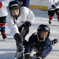 Photo - Members of the Oklahoma City Youth Hockey Association's 8 and Under League go for the puck Saturday.
