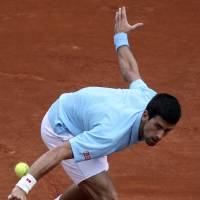 Photo - Serbia's Novak Djokovic returns the ball to France's Jeremy Chardy during their second round match of  the French Open tennis tournament at the Roland Garros stadium, in Paris, France, Wednesday, May 28, 2014. (AP Photo/David Vincent)