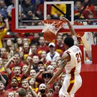 Photo - Iowa State guard Will Clyburn, right, dunks over Kansas State guard Will Spradling during the first half of an NCAA college basketball game, Saturday, Jan. 26, 2013, in Ames, Iowa. (AP Photo/Matthew Putney)