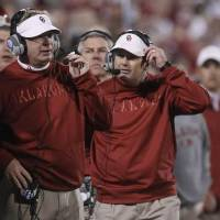 Photo -  Oklahoma head coach Bob Stoops, right, and defensive coordinator Mike Stoops, left, talk on their headphones on the sidelines in the fourth quarter of an NCAA college football game against Notre Dame in Norman, Okla., Saturday, Oct. 27, 2012. Notre Dame won 30-13.(AP Photo/Sue Ogrocki)