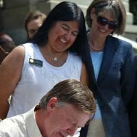 Photo - Colorado Governor John Hickenlooper  signs into law an expansion of Medicaid eligibility that's expected to add 160,000 adults to public health care assistance, at the state Capitol, in Denver, Monday May 13, 2013. The expansion is part of the federal health care overhaul. Medicaid bill sponsor, state senator Irene Aguilar, MD, looks on, top left. (AP Photo/Brennan Linsley)