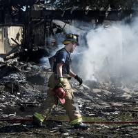 Photo - A Bryan firefighter walks across the smoking rubble of a Knights of Columbus Hall in Bryan, Texas, Saturday, Feb. 16, 2013.  Two Texas fire lieutenants have died of burns after battling a lodge hall fire, and two are hospitalized, a city official said Saturday. (AP Photo/Bryan College Station Eagle, Stuart Villanueva)