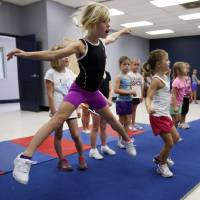 Photo - Ella Hodges, 7, practices leaps at a cheer and tumbling camp this week sponsored by Norman's Parks and Recreation Department. PHOTO BY STEVE SISNEY, THE OKLAHOMAN  STEVE SISNEY