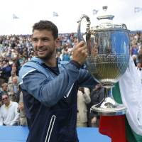 Photo - FILE - In this June 15, 2014, file photo, Grigor Dimitrov, of Bulgaria, poses with the trophy after his win against Feliciano Lopez, of Spain, at the end of their Queen's Club grass court championships singles final tennis match in London  Heading into the U.S. Open, Roger Federer, Rafael Nadal, Novak Djokovic and Andy Murray have won 36 of the past 38 Grand Slam titles, a stretch dating to the 2005 French Open. Nowadays, there seems to be a growing sense _ or hope, maybe _ among the best of the rest on the men's tennis tour that the quartet might be more vulnerable than ever.  (AP Photo/Sang Tan, File)