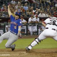 Photo - New York Mets' David Wright (5) starts his slide to home plate to score as Arizona Diamondbacks' Miguel Montero, right, drops the ball during the fifth inning of a baseball game on Monday, April 14, 2014, in Phoenix. (AP Photo/Ross D. Franklin)