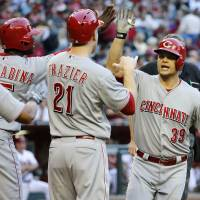 Photo - Cincinnati Reds' Devin Mesoraco (39) is congratulated by teammates Todd Frazier (21), Ramon Santiago, left, and Roger Bernadina after hitting a grand slam against the Arizona Diamondbacks during the second inning of a baseball game, Friday, May 30, 2014, in Phoenix. (AP Photo/Matt York)