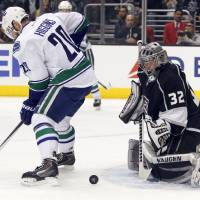 Photo - Vancouver Canucks left wing Chris Higgins (20) looks for the puck on a rebound by Los Angeles Kings goalie Jonathan Quick (32) during the first period of an NHL hockey game on Saturday, Jan. 4, 2014, in Los Angeles. (AP Photo/Alex Gallardo)