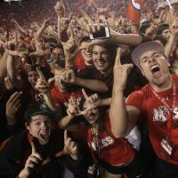 Photo -   Utah fans celebrate on the field at the end of the fourth quarter of an NCAA football game with BYU Saturday, Sept. 15, 2012, in Salt Lake City. Utah received a penalty after the crowd rushed the field before the end of the game. Utah defeated BYU 24-21. (AP Photo/Rick Bowmer)