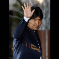 Photo -   FILE - In this Tuesday, Oct. 2, 2012, Bolivia's President Evo Morales waves to photographers upon his arrival to the Summit of South American and Arab Countries in Lima, Peru. Morales said Friday, Oct. 12, 2012, during a ceremony marking