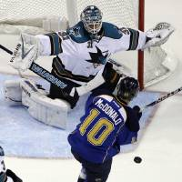Photo -   St. Louis Blues' Andy McDonald (10) is hit with the puck as San Jose Sharks goalie Antti Niemi, of Finland, defends during the first period in Game 2 of an NHL Stanley Cup first-round hockey playoff series Saturday, April 14, 2012, in St. Louis. (AP Photo/Jeff Roberson)