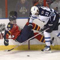 Photo - Winnipeg Jets' Dustin Byfugilen (33) knocks Florida Panthers' Tomas Kopecky (33) to the ice during the third period of a NHL hockey game in Sunrise, Fla., Thursday, Dec. 5, 2013. The Panthers won 5-2. (AP Photo/J Pat Carter)