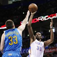 Photo - New Orleans Hornets forward Ryan Anderson (33) defends as Oklahoma City Thunder forward Kevin Durant (35) shoots during the second quarter of an NBA basketball game in Oklahoma City, Wednesday, Feb. 27, 2013. (AP Photo/Alonzo Adams)