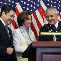Photo - House Democratic Leader Nancy Pelosi, D-Calif., center, is seen with Guatemalan President Otto Molina, right, and Honduran President Juan Hernández on Thursday, July 24, 2014 on Capitol Hill in Washington. The Obama administration is weighing giving refugee status to young people from Honduras as part of a plan to slow the influx of unaccompanied minors arriving at the U.S.-Mexico border, White House officials said Thursday. The plan would involve screening youths in Honduras, one of the world's most violent nations, to determine whether they qualify for refugee status. (AP Photo/Lauren Victoria Burke)