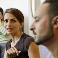 Photo - Members of the Yazidi community in LIncoln, Neb., Iekham Safar, left, her husband Ismaeil Khalaf, right, and Ismaeil's sister Gulie Khalaf, discuss the plight of the Yazidis in Iraq, Tuesday, Aug. 12, 2014, in Lincoln, Neb. Half a world away from the turmoil in Iraq, the largest concentration of Yazidis in United States is trying desperately to rescue their relatives. The first members of the religious minority group came the Lincoln, Nebraska, in the 1990s, and more than 200 families have now made it their home. The number could swell again if the group succeeds in winning asylum for the refugees who are fleeing from violence. (AP Photo/Nati Harnik)