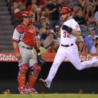 Photo - Los Angeles Angels' Josh Hamilton, right, scores on a single by Howie Kendrick as Philadelphia Phillies catcher Carlos Ruiz looks on during the sixth inning of a baseball game, Wednesday, Aug. 13, 2014, in Anaheim, Calif. (AP Photo/Mark J. Terrill)