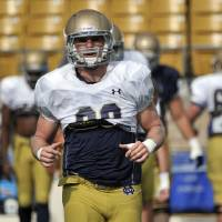 Photo - In this Aug. 19, 2014, photo, Notre Dame linebacker Joe Schmidt loosens up during media day practice of an NCAA college football team in South Bend, Ind. Schmidt doesn't believe he's made it because he's now starting middle linebacker. The 6-foot, 235-pound senior says he doesn't ever want to feel like he's made it.  (AP Photo/Joe Raymond)