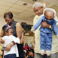 Photo - Abria Glenn is embraced by her parents, Gregory and Anbria Glenn, after being surprised with her Make-A-Wish Foundation trip to Walt Disney World Resort during an assembly at Stanley Hupfeld Academy in Oklahoma City. Her father is holding a doll made in her late brother Gregory Dwayne's likeness.  Photo by PAUL HELLSTERN, The Oklahoman