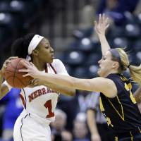 Photo - Iowa guard Melissa Dixon, right, fouls Nebraska guard Tear'a Laudermill in the first half of an NCAA college basketball game in the finals of the Big Ten women's tournament in Indianapolis, Sunday, March 9, 2014. (AP Photo/Michael Conroy)