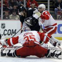 Photo - Detroit Red Wings goalie Jimmy Howard (35) stops a shot by Pittsburgh Penguins' Deryk Engelland (46) as Red Wings' Jakub Kindl (4) helps defend the goal during the first period of an NHL hockey game Thursday, March 20, 2014 in Detroit. (AP Photo/Duane Burleson)