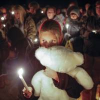 Photo - Lexi Umbarger clutches a teddy bear during a candlelight vigil in Parsons, Kan., on Wednesday, Nov. 27, 2013 for Cami Umbarger and her three young children – Hollie, Jaxon and Averie, who were found murdered in their Parsons home on Monday. David Cornell Bennett Jr. of Cherryvale was arrested on Tuesday in connection with the murders. Lexi Umbarger is the niece of Cami Umbarger and was one of nearly 200 people who turned out near the crime scene for the vigil. (AP Photo/The Wichita Eagle, Travis Heying)