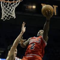 Photo - Chicago Bulls' Nate Robinson (2) puts up a shot against Milwaukee Ersan Ilyasova, left, during the first half of an NBA basketball game Wednesday, Jan. 30, 2013, in Milwaukee. (AP Photo/Jeffrey Phelps)