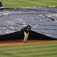Photo - Field crew members pull the tarpaulin as heavy rains sweep over Coors Field and halt play in the fourth inning of a baseball game between the New York Yankees and Colorado Rockies in Denver on Thursday, May 9, 2013. (AP Photo/David Zalubowski)