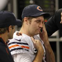 Photo - Chicago Bears quarterback Jay Cutler, center, reacts as he sits on the bench after getting injured during the second half of an NFL football game against the Minnesota Vikings Sunday, Dec. 9, 2012, in Minneapolis. (AP Photo/Andy King)