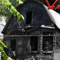 Photo - Firefighters pick through the rubble of a burned out home as they look for clues to a fire that authorities say killed six people in Newark, N.J., Sunday, June 15, 2014. The Essex County prosecutor's office says the fast-moving fire that roared through a single-family home in New Jersey's largest city, broke out at around 4 a.m. Sunday. (AP Photo/Mel Evans)