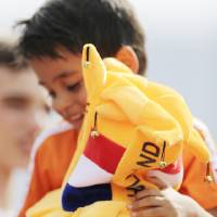 Photo - A young fan of the Netherlands soccer team sits on his father's shoulders as they watch from the stands during a training session in Rio de Janeiro, Brazil, Saturday, June 7, 2014. The Netherlands had their first training session open to fans at the Brazilian club Flamengo training complex. The Netherlands plays in group B of the 2014 soccer World Cup. (AP Photo/Wong Maye-E)