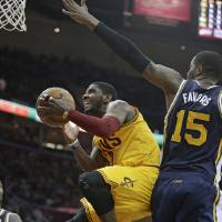 Photo - Cleveland Cavaliers' Kyrie Irving, left, jumps to the basket against Utah Jazz's Derrick Favors (15) during the second quarter of an NBA basketball game on Friday, Feb. 28, 2014, in Cleveland. (AP Photo/Tony Dejak)