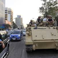 Photo - Egyptian army soldiers sit on top of an armored personnel carrier on a street in Cairo, Egypt, Saturday, Sept. 7, 2013. (AP Photo/Khalil Hamra)