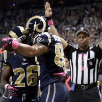 Photo -   St. Louis Rams tight end Lance Kendricks is congratulated by Daryl Richardson, left, after catching a 7-yard pass for a touchdown during the first quarter of an NFL football game against the Arizona Cardinals, Thursday, Oct. 4, 2012, in St. Louis. (AP Photo/Tom Gannam)