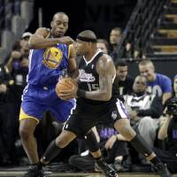 Photo -   Sacramento Kings center DeMarcus Cousins, right, goes to the basket against Golden State Warriors forward Carl Landry during the first half of an NBA basketball game in Sacramento, Calif., Monday, Nov. 5, 2012. (AP Photo/Rich Pedroncelli)