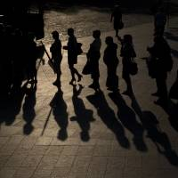 Photo - People cast shadows on the pavement while waiting for a bus during an outdoor memorial concert for victims of the Malaysian Airlines Flight 17 air crash in downtown Kharkiv, Ukraine, Thursday, July 24, 2014. Two military aircraft carrying remains of victims from the Malaysian plane disaster departed for the Netherlands on July 24, while Australian and Dutch diplomats joined to promote a plan for a U.N. team to secure the crash scene which has been controlled by pro-Russian rebels.(AP Photo/Vadim Ghirda)