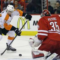 Photo - Carolina Hurricanes goalie Justin Peters (35) guards the net against Philadelphia Flyers' Matt Read (24) during the first period of an NHL hockey game in Raleigh, N.C., Tuesday, Nov. 5, 2013. (AP Photo/Gerry Broome)