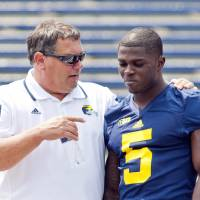 Photo - Michigan head coach Brady Hoke, left, speaks with freshman cornerback Jabrill Peppers (5) after a team photo during the NCAA college football team's preseason media day, Sunday, Aug. 10, 2014, at Michigan Stadium in Ann Arbor, Mich. (AP Photo/Tony Ding)